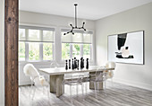 White dining room with wooden table, Ghost chairs, black pendant and modern art on wall