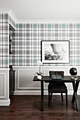 Desk in front of wall with tartan wallpaper and panelled wainscoting
