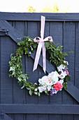 Kranz aus Blättern und Blüten an Holztür