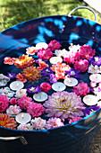 Summer flowers and tealights floating in metal tub