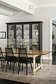 Glass-fronted cabinets and antique dining table with wooden chairs in dining area