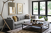 Grey corner sofa, standard lamp and coffee table in front of terrace doors