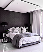 Double bed in bedroom with shiny tiled floor, black wallpaper and ceiling panel