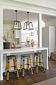 White breakfast bar with bar stools below pendant lamps with glass lampshades