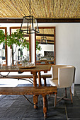 Rustic wooden table with benches and armchair on roofed terrace