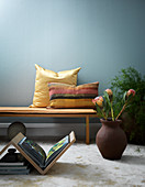 Book table and floor vase in front of bench with cushions