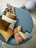 Top view of round blue easy chair with scatter cushions in warm shades