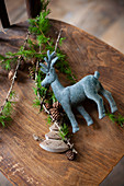 Reindeer figurine and larch twigs on wooden chair