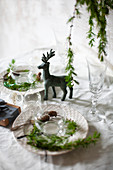 Place settings decorated with larch twig on table set for Christmas meal