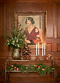 Festively decorated console table below painting on wooden wall panelling