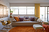 Sofa and classic chair in living room with orange accents