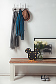 Lamp, roses and picture on wooden bench below coat pegs in hall