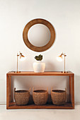 Bamboo baskets, table lamps and vase on wooden console table below round mirror on wall