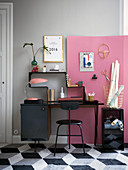 Study are with black furniture against grey wall and pink pin board