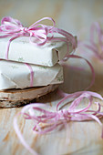 Gifts wrapped in white paper and pink ribbon