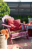 Pink deck chair with fur blanket and cushion on comfortable terrace