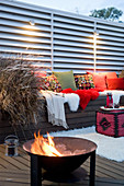 Bench with cushions under lights and fire bowl on terrace