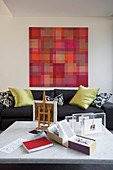 Pixellated artwork in shades of red above sofa