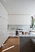 White, modern kitchen with marble island counter