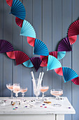 Colourful garland of paper fans above party buffet