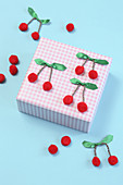 Hand-crafted cherries decorating wrapped gift
