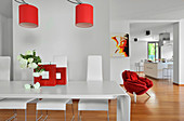 Modern dining room in open-plan interior with red accents