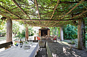 Table and wooden benches below climber-covered pergola with seating area in front of fireplace in background