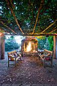 Runder Tisch mit Holzbänken unter bewachsener Pergola, vor Kamin mit Feuer