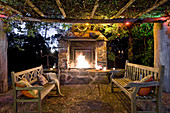 Round table and wooden benches below climber-covered pergola in front of open fire in fireplace