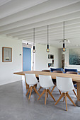 Moderner offener Wohnraum mit Betonboden und Balkendecke