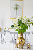 White lilac in golden vase and golden ornaments on table