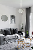 Delicate golden tables in front of sofa in grey living room