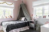 Bed with velvet bedspread and canopy in girl's bedroom with pink walls