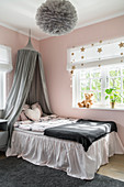 Bed with valance and canopy in girl's bedroom in pink and grey