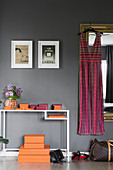 Dress hanging on mirror next to console table and orange boxes