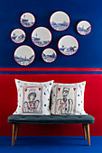 Cushions on bench below decorative wall plates on blue-and-red wall