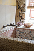Sink covered in mosaic tiles and pebbles