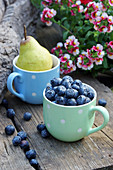 Blueberries and pear in mugs on wooden bench outdoors
