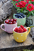 Blueberries, cherries and raspberries in mugs on wooden bench outdoors