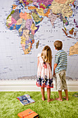 Two children standing in front of map of the world