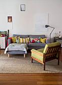 Graues Polstersofa mit Kissen, passender Polstertisch und gelb-grüner Sessel