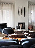 Designer armchairs and cowhide rug in front of fireplace in living room