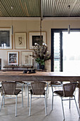 Rustic wooden dining table, rattan chairs and wrought-iron chandelier