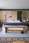 Rustic bedroom bench, double bed and wall panels made from vintage wooden doors in bedroom