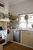 Kitchen with cream base units and gas cooker in niche
