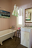 Vintage bathtub, sink on washstand and girl's dresses on clothes line in bathroom