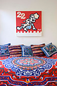 Colourful bedspread and scatter cushions on bed below comic-style artwork