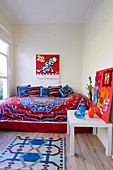 Colourful bedspread and scatter cushions on bed below comic-style artwork behind vases and felt collage on side table