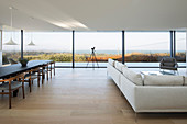 Pale sofa set and dining area in open-plan interior with glass wall
