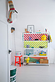 Shelves with brightly coloured back wall in child's bedroom